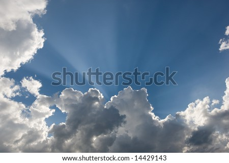 Beautiful sun rays in blue sky, downy clouds - stock photo