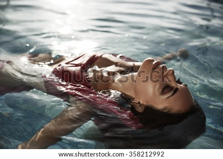 Beautiful sun-tanned woman with closed eyes in the water enjoys her vacation by taking sunbathes in the swimming poll - stock photo