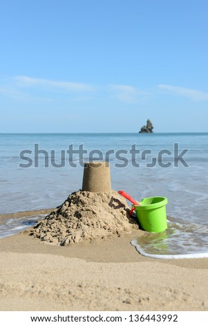 beautiful  sunny day at the beach with Sandcastle, bucket and spade - stock photo
