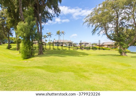 Beautiful sunny green golf course with palm trees and vacation houses in Maui, Hawaii. - stock photo