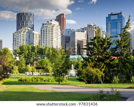 Beautiful sunny summer day in Calgary Downtown. Beautiful view of downtown of the biggest Alberta city - Calgary. Image taken from Prince's Island park with it's fountains and mature trees. - stock photo