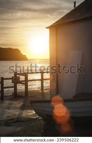 Beautiful sunrise behind fishing hut in Lulworth Cove with added lens flare - stock photo