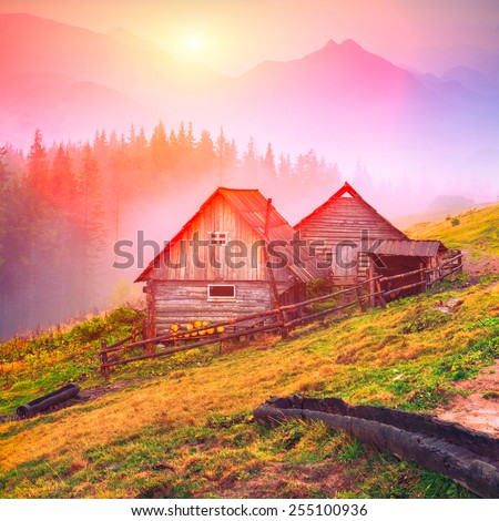 Beautiful sunrise in Carpathian mountains with nature wooden houses on a forest hill.  - stock photo