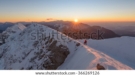 Beautiful sunrise in the winter mountains. Male hiker waiting for the sunrise.