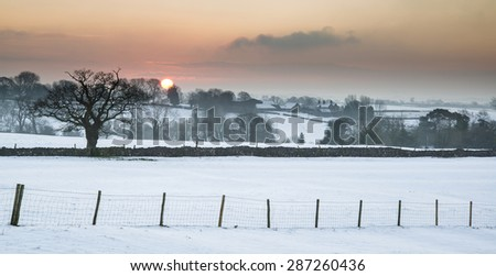 Beautiful sunrise landscape over snow covered Winter countryside - stock photo