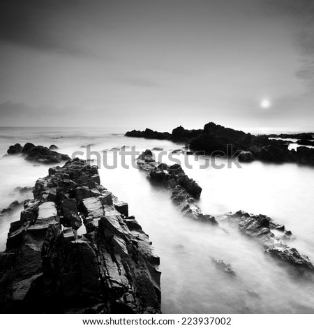 Beautiful sunrise landscape seascape over rocky coastline. Black & White minimalist seascape with rocks in black and white  - stock photo