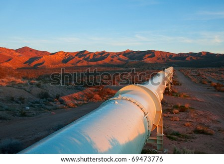 Beautiful sunrise lighting on a pipeline in the Mojave Desert. - stock photo