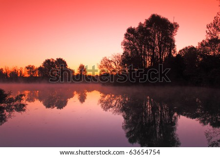 Beautiful sunrise over a lake with fog or mist - stock photo