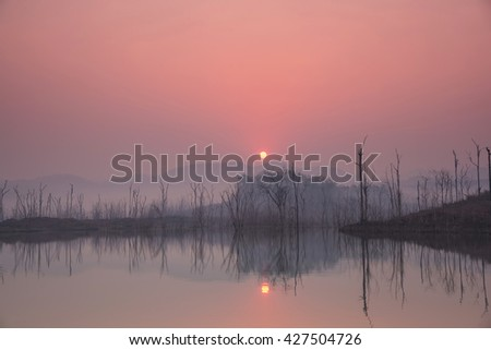 Beautiful sunrise over a lake with mist faded,Thailand. - stock photo