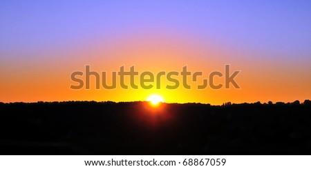 Beautiful Sunrise over a Silhouetted Horizon - stock photo