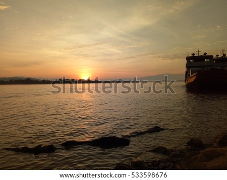 Beautiful sunrise over Mae Khong river with chinese transportation on river bay.