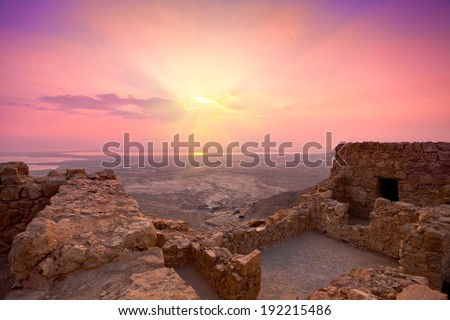 Beautiful sunrise over Masada fortress. Ruins of King Herod's palace in Judaean Desert. - stock photo