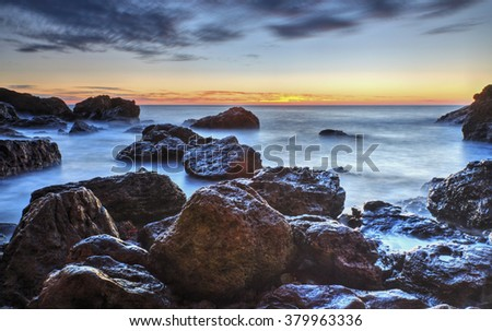 Beautiful sunrise over the sea and rocky shore