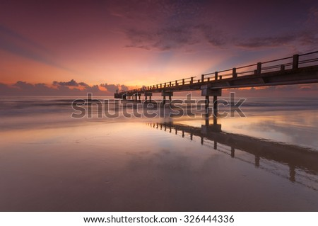 Beautiful sunrise seascape with amazing reflection on the sand. Soft focus and motion blur due to long exposure.
