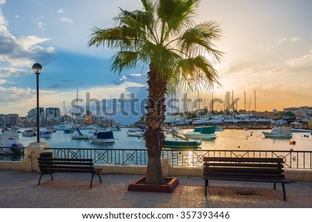 Beautiful sunrise with benches, palm tree and sailboats at Sliema bay, Malta - stock photo