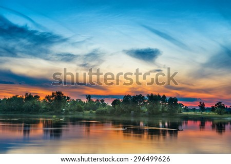 Beautiful sunset above a big river with green forest on the other coast and reflection on water - stock photo