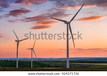 Beautiful sunset above the windmills on the field - stock photo