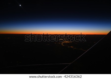 Beautiful sunset and city lights from airplane window