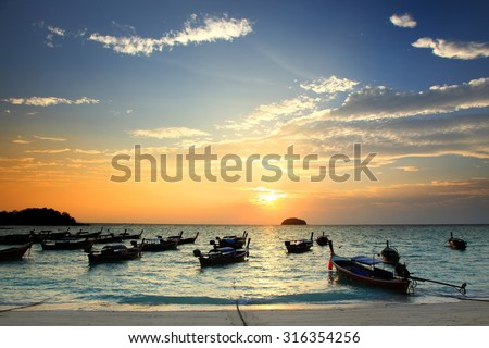 Beautiful sunset and Thai local fishing boats on seaside at Lipe island beach of the Andaman sea, in Satun Province of Thailand. - stock photo