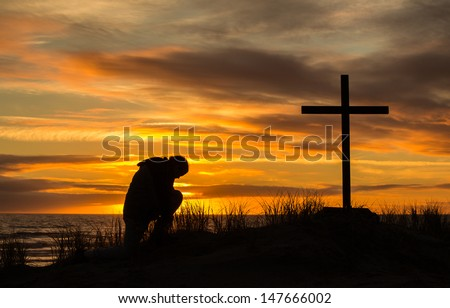 Beautiful sunset as man bows down to pray God before a cross. - stock photo