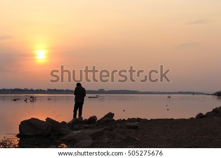 Beautiful sunset at Mekong river bank. Young asian man standing at riverside. Warmth and peaceful, relaxation feeling, colorful nature landscape background