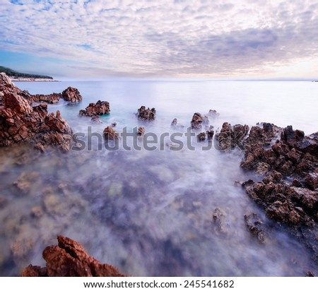 Beautiful sunset at romantic tropical beach cove with stones and water in motion - stock photo