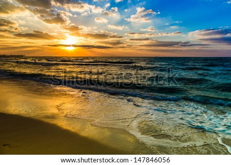 Beautiful sunset at the beach, amazing colors, light beam shining through the cloudscape over the arabian gulf seascape, united arab emirates. Dubai sea and beach