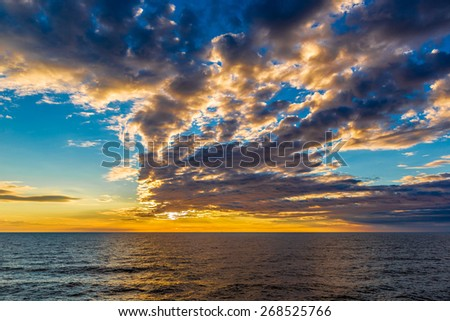 Beautiful sunset at the beach, amazing colors, light beam shining through the cloudscape over the arabian gulf seascape, united arab emirates. - stock photo