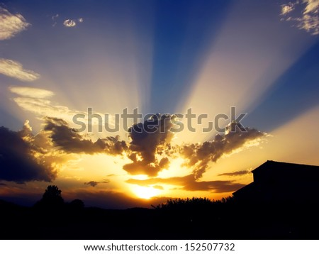 Beautiful sunset at the country, with a rural home silhouette and sun rays between clouds - stock photo