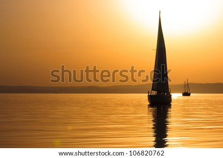 Beautiful sunset at the sea with boats - stock photo
