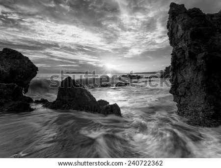 Beautiful sunset at the stone beach in black and white - stock photo