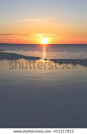 Beautiful sunset behind the rocks in the water. Those stones are like small island across the water. Glowing sun is going down in Finland. Image has a vintage effect applied. - stock photo