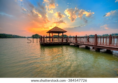 Beautiful Sunset clouds over the Wetland Park boathouse in the Putrajaya, Malaysia. Soft focus during long eposure.