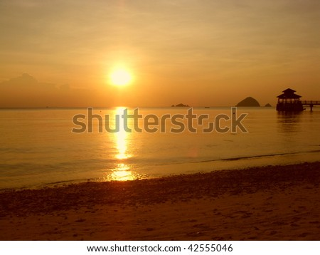 Beautiful sunset in a beach with a pier - stock photo
