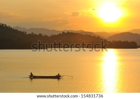 Beautiful sunset in Asia with a river and a boat on it - stock photo