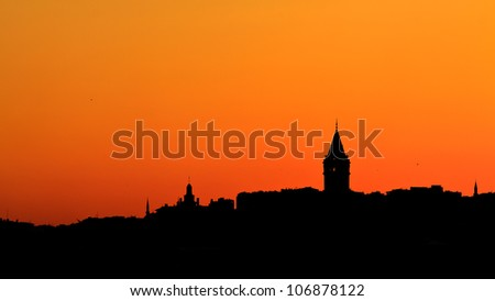 Beautiful sunset in Istanbul, Turkey with Galata Tower and Mosque minaret on the horizon, contrejour view - stock photo