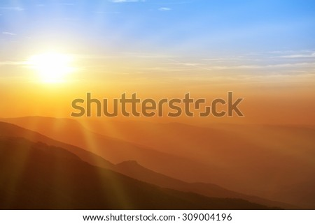 Beautiful sunset in the mountains. Colorful landscape with sun, sunrays and blue sky - stock photo