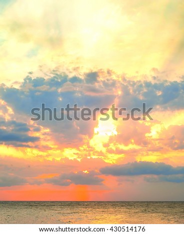 Beautiful sunset in the sea with sunbeam and many colors - stock photo