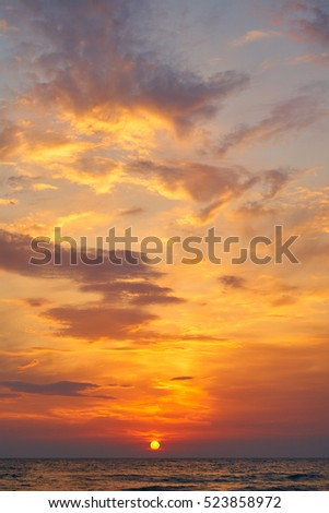 Beautiful sunset in tropical sea. Sun through clouds