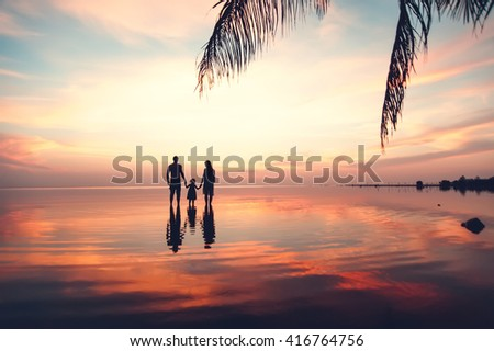 Beautiful sunset landscape with silhouettes of family at the sea - stock photo