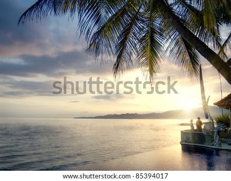 Beautiful sunset on a Balinese coastline with luxury villa - stock photo