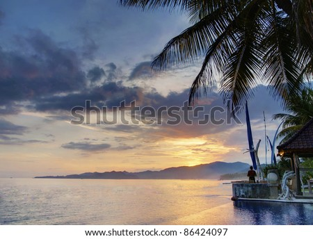 Beautiful sunset on a Balinese coastline with luxury villa - stock photo