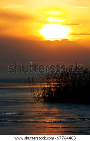 Beautiful sunset on a frozen lake - stock photo
