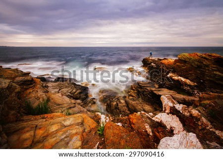 Beautiful sunset on a rocky ocean shore - stock photo