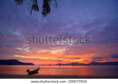 Beautiful sunset on a tropical beach with a boat. - stock photo