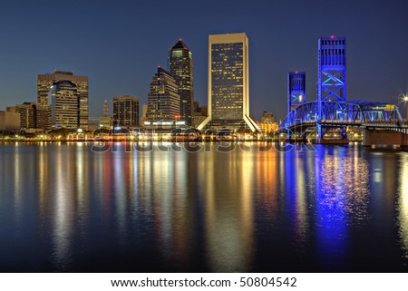 Beautiful sunset on St. John's River and Jacksonville, Florida skyline showing the John T. Alsop Jr. Bridge - stock photo