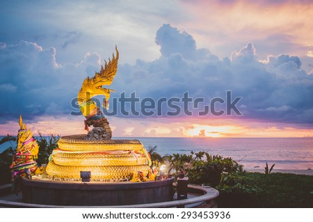 Beautiful sunset on the beach in Thailand, buddhist statue in the form of a dragon on island Phuket on Karon beach - stock photo