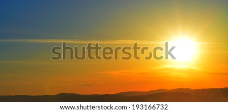 Beautiful sunset over a mountain range in the distance, meditative background
