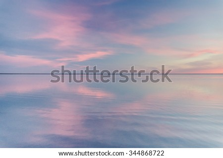 beautiful sunset over calm cold lake - stock photo