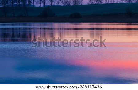 Beautiful sunset over calm lake. Colorful and vibrant landscape of lake shore with reeds. Tranquil landscape useful as background - stock photo